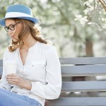 woman sitting on a bench holding tablet and coffee